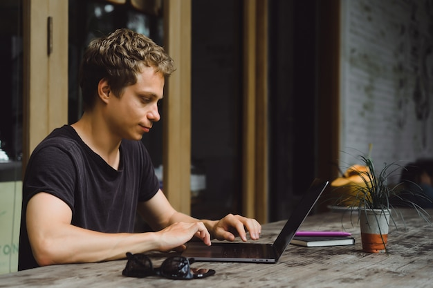 Man aan het werk met een laptop in een café op een houten tafel