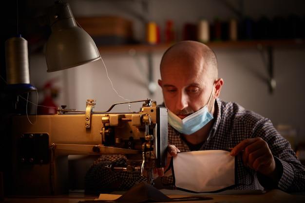 Man aan het werk met een naaimachine die zelfgemaakte gezichtsmasker doet om de verspreiding van het coronavirus te voorkomen en te stoppen