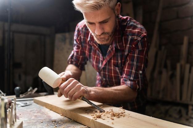 Man aan het werk met hout in werkplaats