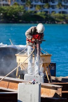 Man aan het werk met jackhammer in een haven
