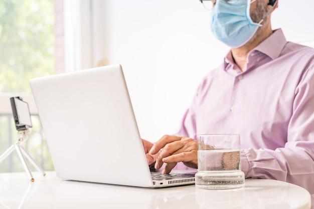 Man aan het werk met laptop en chirurgische masker.
