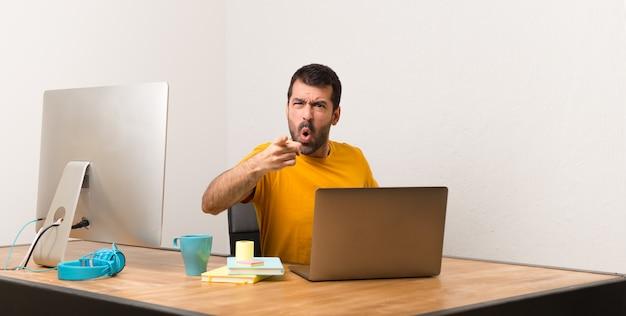 Man aan het werk met laptot in een kantoor gefrustreerd door een slechte situatie en wijst naar de voorkant