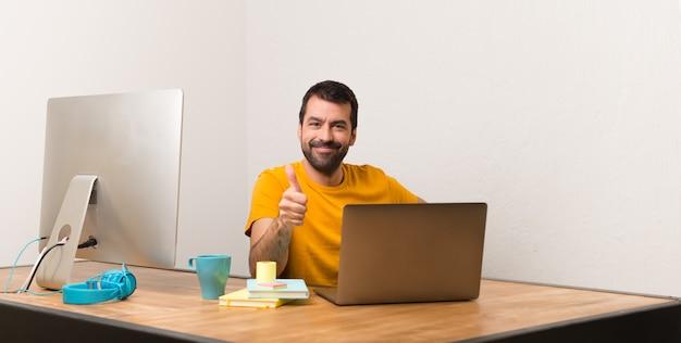 Man aan het werk met laptot in een kantoor geven een duim omhoog gebaar omdat er iets goeds is gebeurd