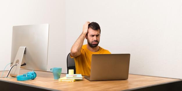 Man aan het werk met laptot in een kantoor met een uitdrukking van frustratie en geen begrip