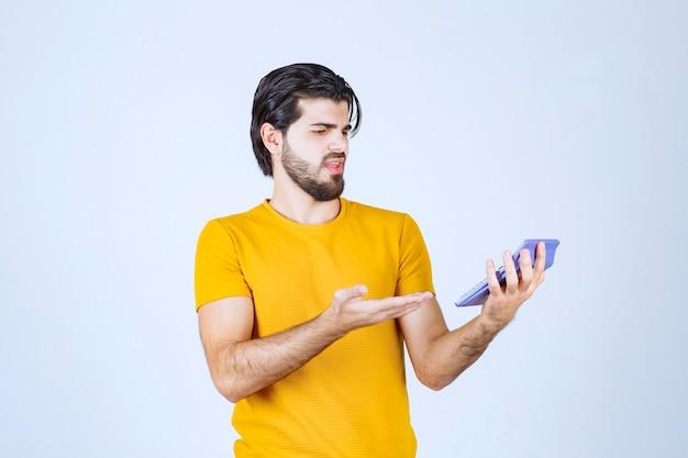 Man aan het werk met rekenmachine en ziet er ontevreden uit.