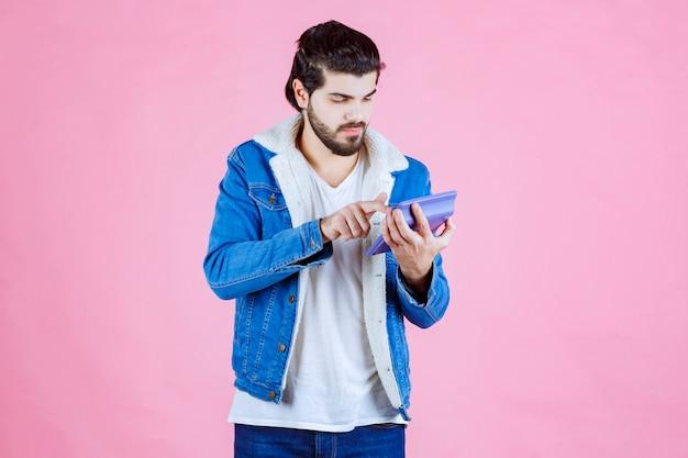 Man aan het werk met rekenmachine en ziet er verward uit