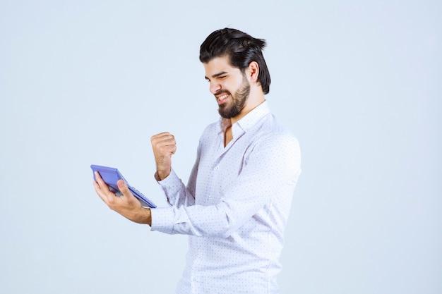 Man aan het werk met rekenmachine ziet er succesvol en tevreden uit.
