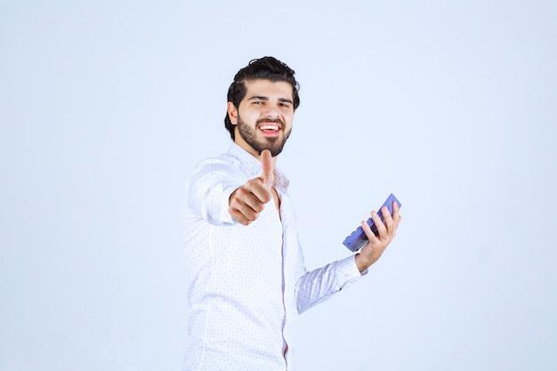 Man aan het werk op bluee rekenmachine en ziet er druk uit.