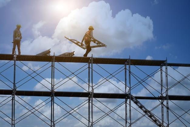 Man aan het werk op de bouwplaats met steiger en gebouw met hemelachtergrond, steigers voor bouwfabriek