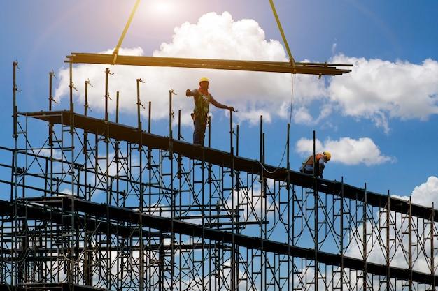 Man aan het werk op de bouwplaats met steiger en gebouw, steigers voor bouwfabriek