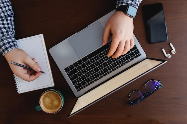 Man aan het werk op de laptop met een kopje koffie, telefoon, thuis schrijven met pen. hoge kwaliteit foto