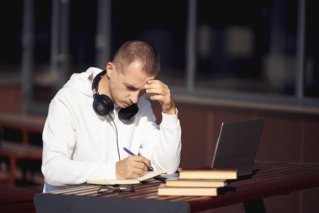 Man aan het werk op een laptop en schrijven in een notitieblok zittend op straat aan een tafel. sociale afstand nemen tijdens het coronavirus