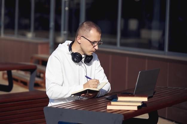 Man aan het werk op een laptop en schrijven in een notitieblok zittend op straat aan een tafel sociale afstand nemen tijdens het coronavirus