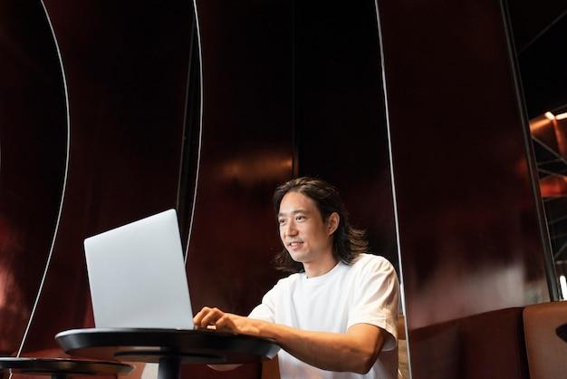 Man aan het werk op een laptop op een moderne co-working-ruimte