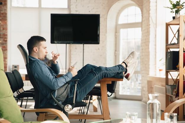 Man aan het werk op kantoor in comfortabele kleding, ontspannen houding en rommelige tafel