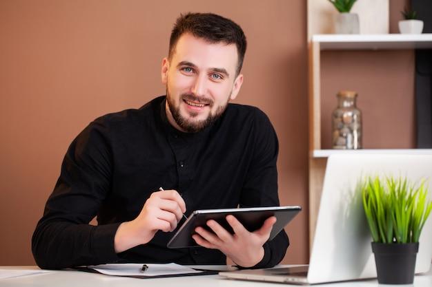 Man aan het werk op kantoor op laptop