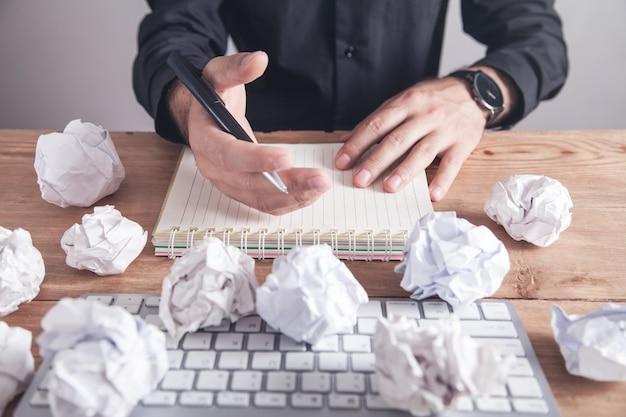 Man aan het werk op kantoor. verfrommelde papieren ballen op tafel