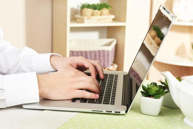 Man aan het werk op laptop op houten tafel op interieur oppervlak