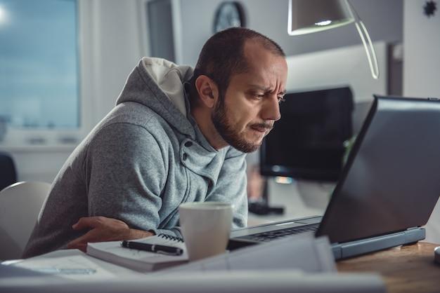 Man aan het werk op laptop thuis
