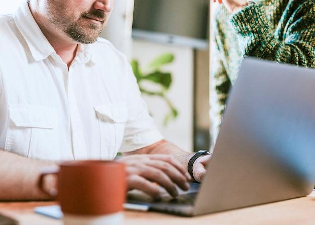 Man aan het werk op zijn laptop in een café