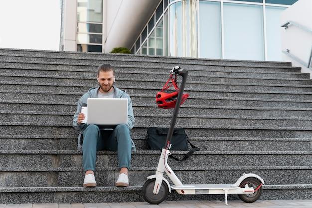 Man aan het werk op zijn laptop naast zijn scooter
