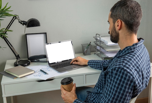 Man aan het werk terwijl hij koffie drinkt