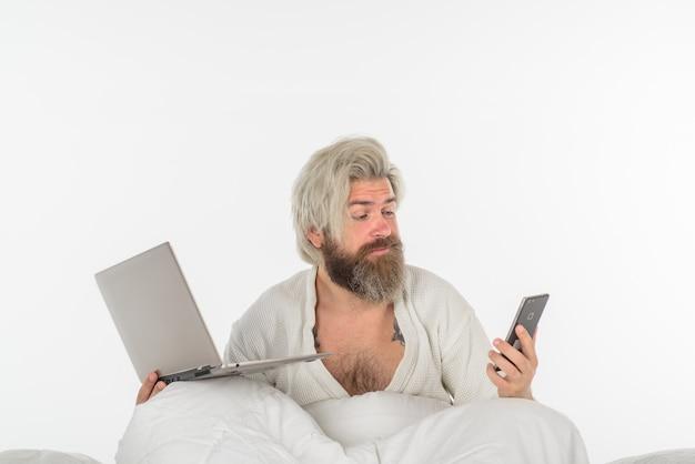 Man aan het werk vanuit bed werken vanuit huis zelfisolatie verwarde man in bed werken met laptop 's ochtends