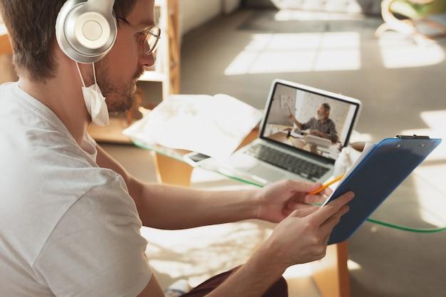 Man aan het werk vanuit huis, met behulp van apparaten, remote office concept. jonge zakenman, manager die taken met laptop doet, heeft online conferentie. coronavirus, covid-19 preventie van verspreiding van het virus.