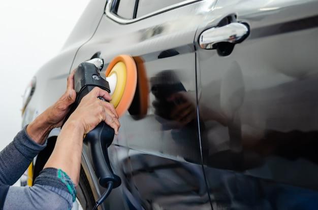 Man aan het werk voor het polijsten, coaten van auto's. polijsten van de auto helpt bij het verwijderen van verontreinigingen op het oppervlak van de auto.