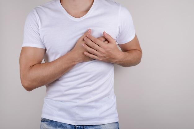 Man aanraken linkerkant van borst met handen geïsoleerde grijze achtergrond