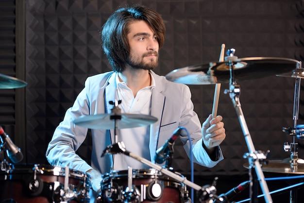 Man achter drum-type installatie in een opnamestudio.