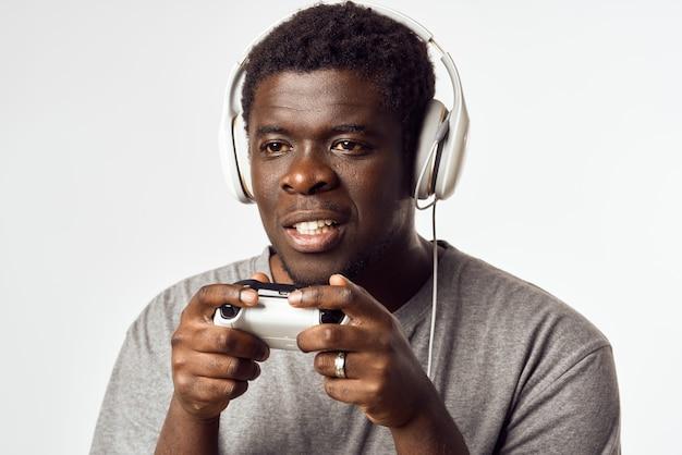 Man afrikaans uiterlijk met gamepad in handen die entertainmenttechnologie speelt