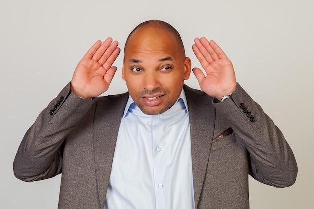 Man afro-amerikaanse zakenman, die zijn hand achter zijn oor houdt, waaruit blijkt dat hij niet hoort, probeert te luisteren naar roddels, luister aandachtig naar het gesprek van iemand anders.