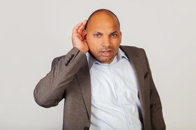 Man afro-amerikaanse zakenman, die zijn hand achter zijn oor houdt, waaruit blijkt dat hij niet hoort