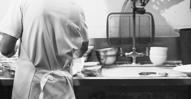 Man afwas schotel op gootsteen in restaurant