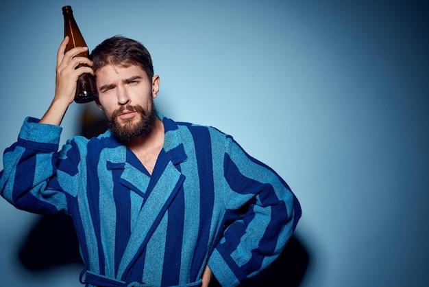 Man alcoholist met een flesje bier in zijn hand en in een blauwe kamerjas