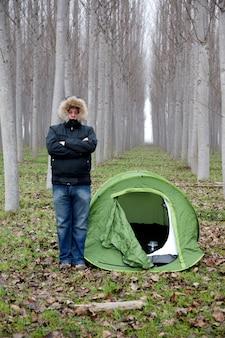 Man alleen in het bos met schuilplaats tent