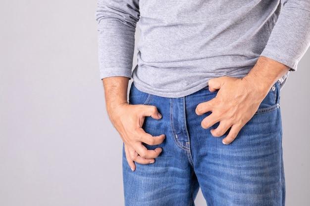 Man als reactie op jeuk of probeert zijn hand te gebruiken en over zijn broek te krabben