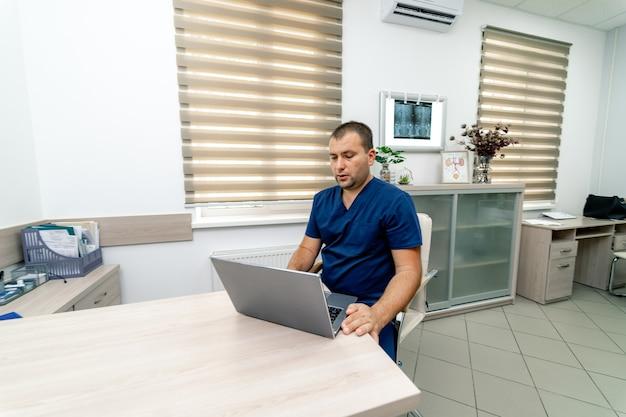 Man arts die videochat geeft aan de cliënt op laptop in het ziekenhuis. pandemische beperkingen.