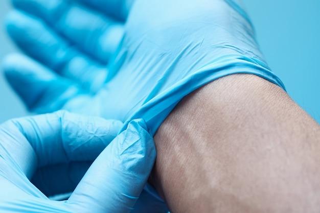 Man arts draagt medische handschoenen, close-up