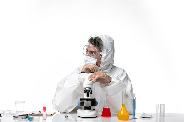 Man arts in beschermend pak en masker met behulp van microscoop op wit
