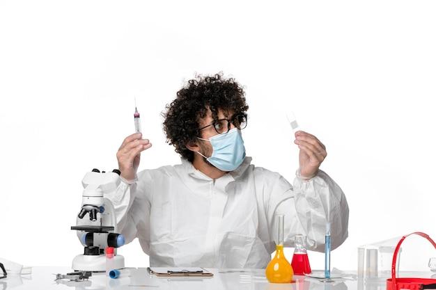 Man arts in beschermend pak en masker werken met injecties op wit