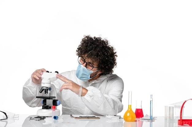 Man arts in beschermend pak en masker werken met microscoop op wit