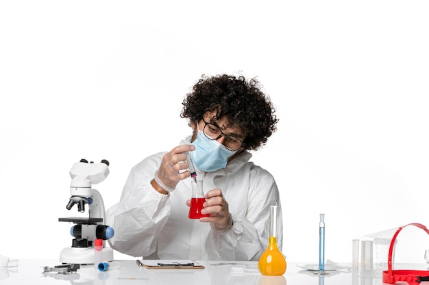 Man arts in beschermend pak en masker werken met oplossingen op wit