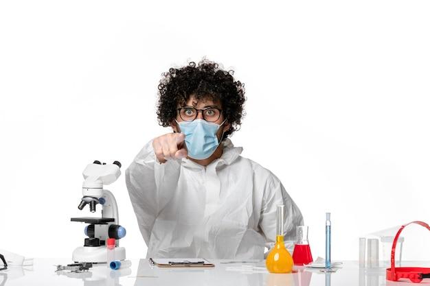 Man arts in beschermend pak en masker wijzend op wit