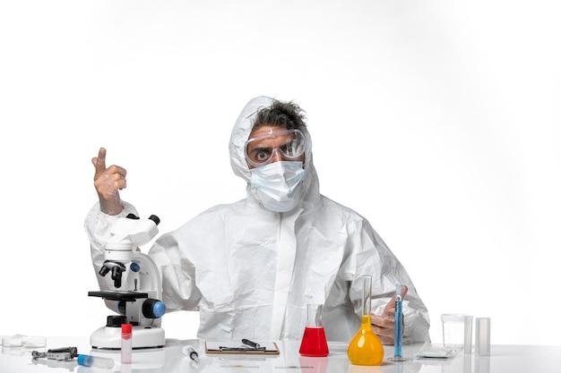 Man arts in beschermend pak en masker zittend op lichtwit