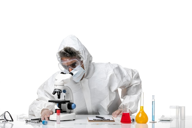 Man arts in beschermend pak en met masker met behulp van microscoop op wit
