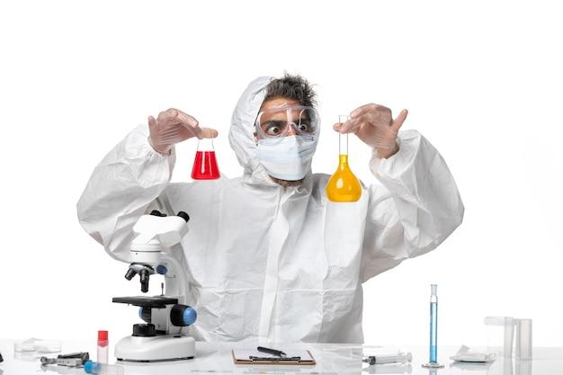 Man arts in beschermend pak en met masker met kolven met oplossingen op wit