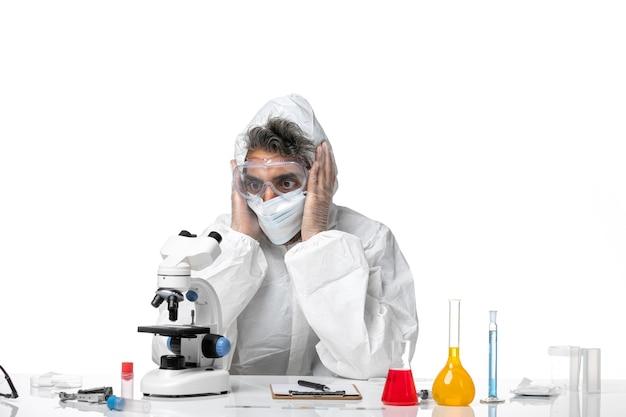 Man arts in beschermend pak en met masker werken met oplossingen op wit