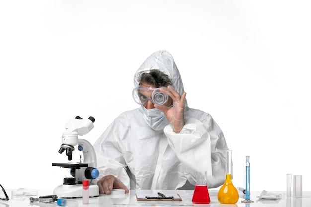 Man arts in beschermend pak en met steriel masker met lege fles op wit on